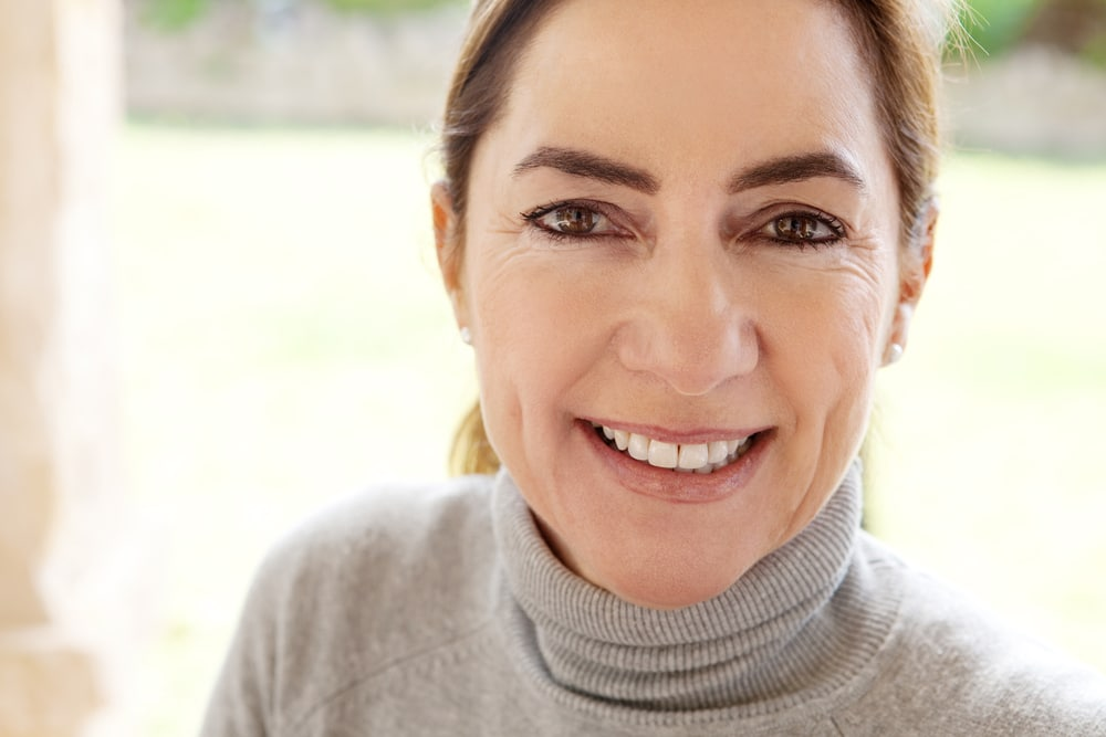 Close up beauty portrait of an attractive joyful and positive mature hispanic woman by a green grass garden during a sunny day at home, smiling and feeling positive.